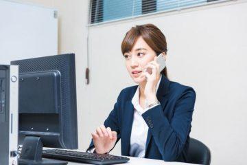 パソコンを見ながら忙しそうに電話をする女性