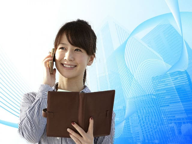 手帳を見ながら電話する女性